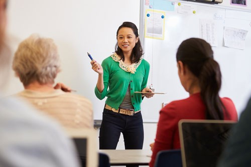 Smiling teacher talking to multi-ethnic students at language class